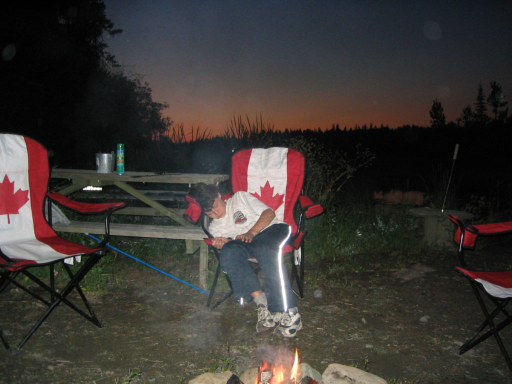 child asleep by campfire